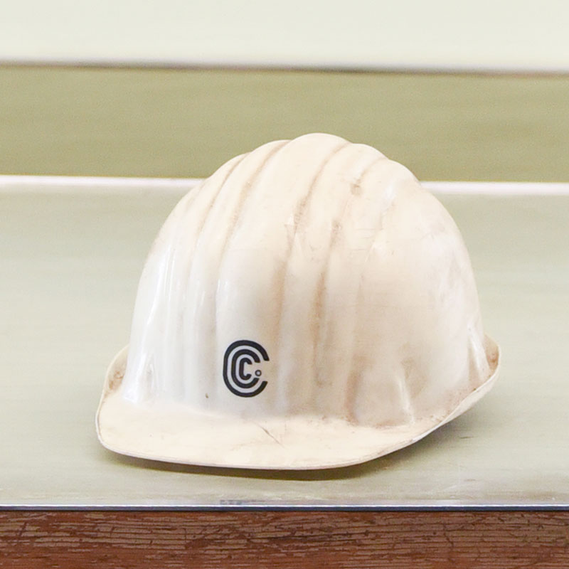 A white hardhat sitting on a desk